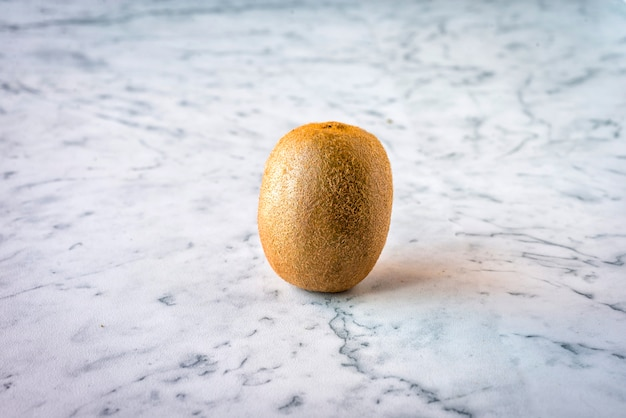 A fresh kiwi on a marble surface