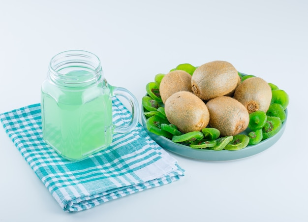 Fresh kiwi in a plate with dried kiwi, drink high angle view on picnic cloth and white background