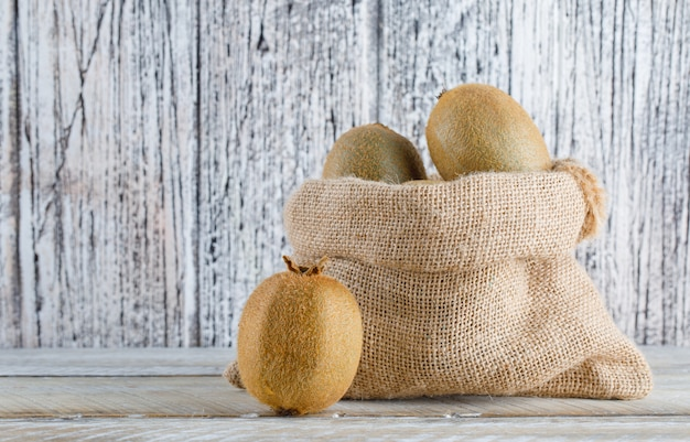 Fresh kiwi in a sack on a wooden table. side view.