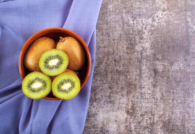 Fresh kiwi top view in ceramic bowl on blue cloth on  surface