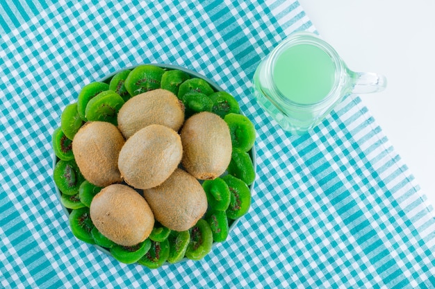 Fresh kiwi with dried kiwi, drink in a plate on picnic cloth and white background, flat lay.