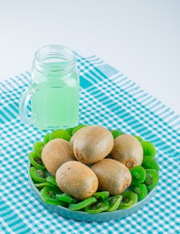 Fresh kiwi with dried kiwi, drink in a plate on picnic cloth and white background, high angle view.