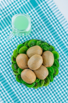 Fresh kiwi with dried kiwi, drink in a plate on picnic cloth and white background, top view.