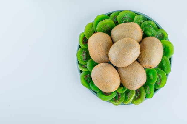 Fresh kiwi with dried kiwi in a plate on white background, flat lay.