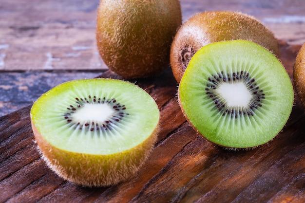Fresh kiwifruit cut in half on a wooden cutting board.