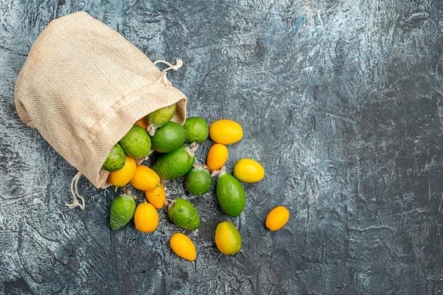 Kumquat freschi dentro e fuori di una piccola borsa bianca caduta