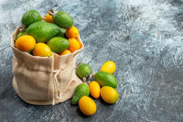 Kumquat freschi dentro e fuori di una piccola borsa bianca