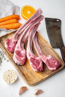 신선한 양고기 커틀릿. 흰색 돌 배경에 당근 오렌지, 허브, 오래된 정육점 칼을 넣은 유기농 고기 스테이크 세트 프리미엄 사진