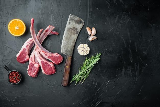 신선한 양고기 커틀릿. 유기농 고기 스테이크 세트, 재료 당근 오렌지, 허브, 검은 돌 테이블, 평면도 평면 누워