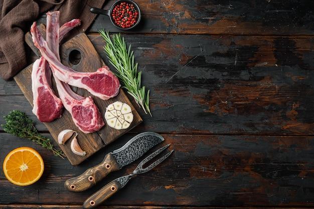 新鮮な子羊のカツレツ。有機ミートステーキセット、材料にんじんオレンジ、ハーブ、古い暗い木製のテーブル、上面図フラットレイ