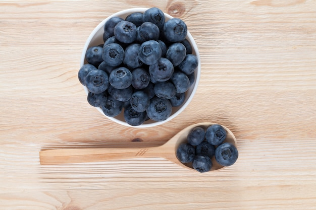 Fresh large and sweet blueberry of a new crop lying in a wooden spoon and a ceramic plate on a wooden table, close-up, top view