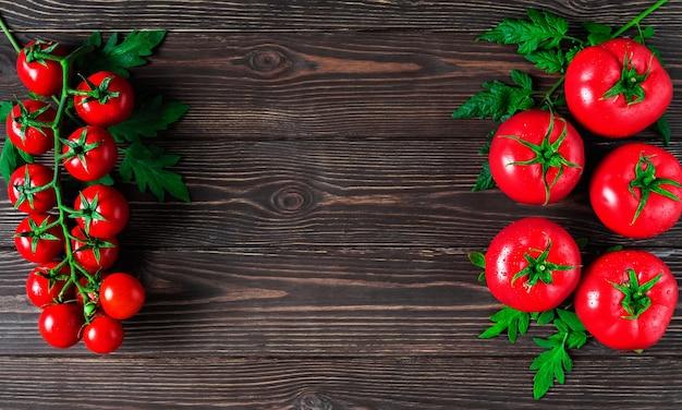 Свежие крупные помидоры и ветка помидоров черри с листьями на темной деревянной поверхности