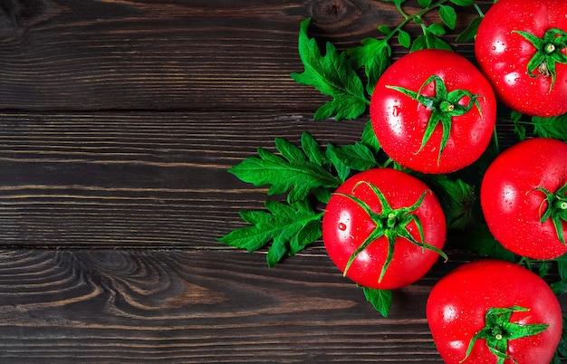 Свежие крупные помидоры с листьями в правой части кадра