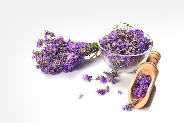 유리 그릇에 신선한 라벤더 무리와 라벤더 꽃. 흰색 배경에 고립.
