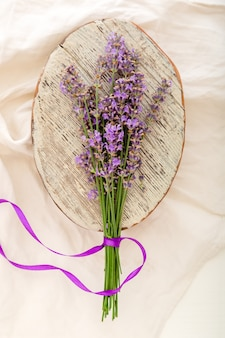 Fresh lavender flower bouquet on old rustic wooden board on fabric. bouquet of lavender tied with ribbon. flatlay french provence style flower blossom. drying lavender flowers.