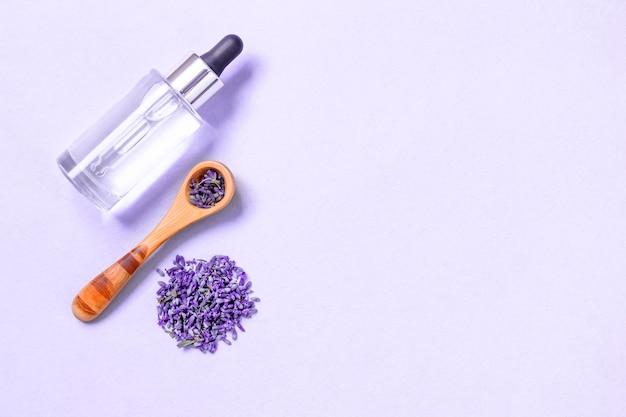 装飾的な小瓶に束とエッセンシャルオイルで結ばれた新鮮なラベンダーの花。自然化粧品。