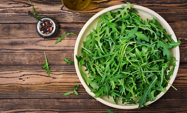 Fresh leaves of arugula in a bowl on a wooden background. flat lay. top view