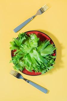 접시에 프리즈 상 추의 신선한 잎과 노란색 테이블에 포크. 상단 및 세로보기