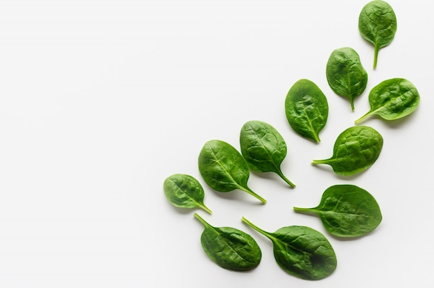 Fresh leaves of spinach are laid out on a white background in the form of a pattern.