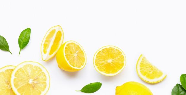 Свежий лимон и кусочки с листьями, изолированные на белом.