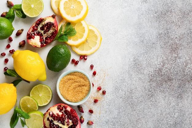 Свежий лимон, лайм, гранат, сушеные цветы чайной розы, чай, тростниковый сахар и листья мятного букета на сером. ингредиенты для приготовления лимонадного напитка, махито или холодного освежающего чая.