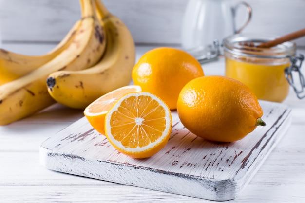 白い木製のテーブルの上のホワイトボード上の新鮮なレモン