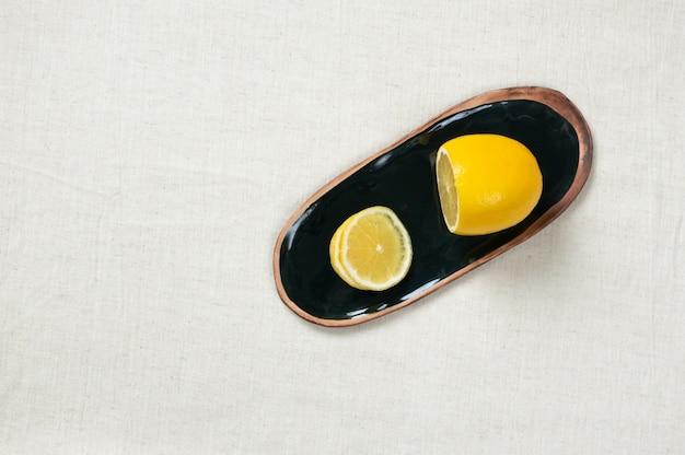 Свежий лимон на блюдце на тканевой скатерти, вид сверху. керамика ручной работы