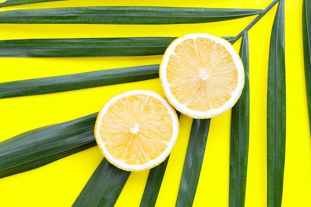 黄色い表面に熱帯のヤシの葉に新鮮なレモン