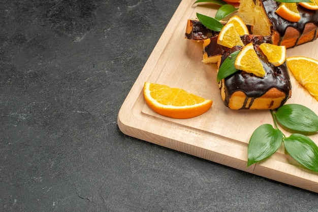 Свежие дольки лимона и свежеиспеченные нарезанные ломтики торта на темном столе
