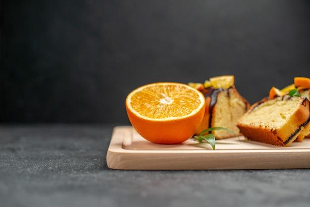Fette di limone fresco e fette di torta tritata appena sfornata sul tavolo scuro