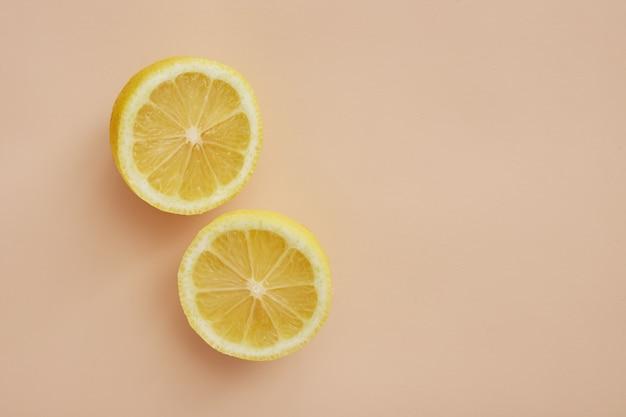 ベージュの背景に2つの部分に分割された新鮮なレモン