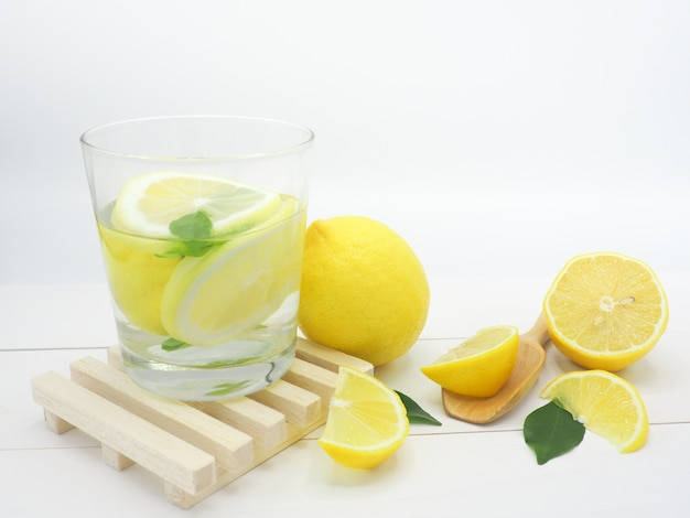 Fresh lemon in water and lemon slice on white wood background