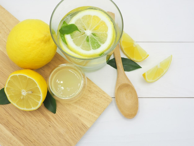 Fresh lemon in water, lemonade and lemon slice on white wood background