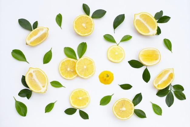 Свежий лимон с зелеными листьями на белом фоне.