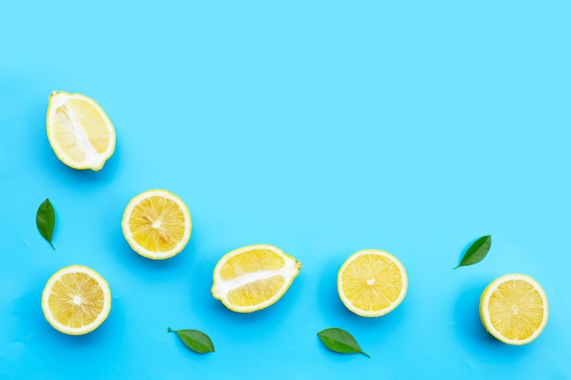Свежий лимон с зелеными листьями на синем фоне.