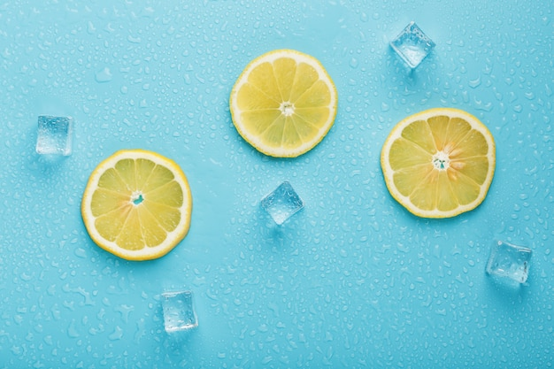 Fresh lemon with ice and drops on a blue background
