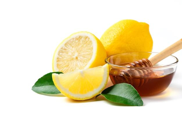 葉と白い壁、成分夏飲料コンセプトに分離された蜂蜜ディッパーと蜂蜜と新鮮なレモン