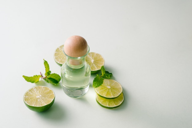 Свежий лимон с эфирным маслом лимона на цветном фоне