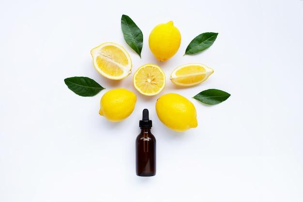 Свежий лимон с эфирным маслом лимона на белом фоне.