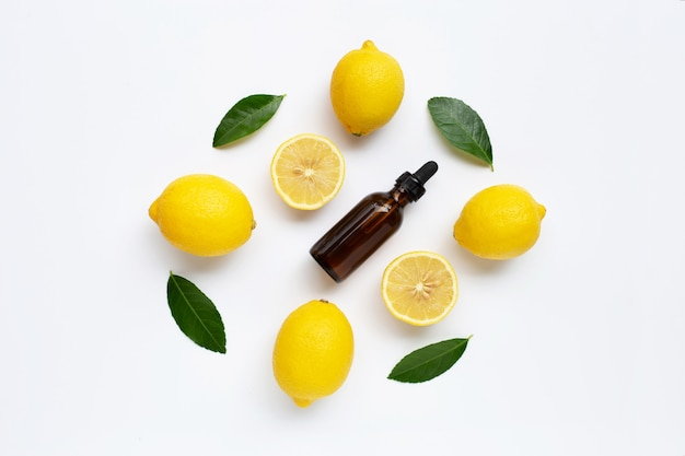Fresh lemon with lemon essential oil on white background.