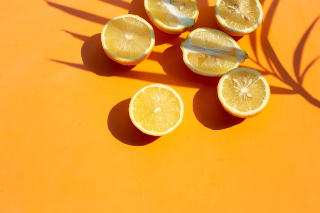 Fresh lemon with palm tree leaf on orange surface