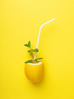 白いわらと黄色の表面にミントの新鮮なレモン