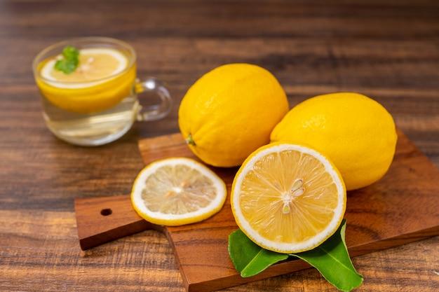 ガラス、ライムまたはモヒートのハーブと一緒に飲む新鮮なレモネード、暑い夏のコピースペースのための木のテーブルにレモンとカクテル