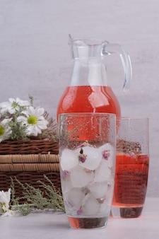 Limonata fresca in cubetti di ghiaccio e di vetro sul tavolo bianco.