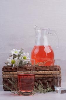 Limonata fresca in vetro e vaso con margherite sul tavolo bianco.