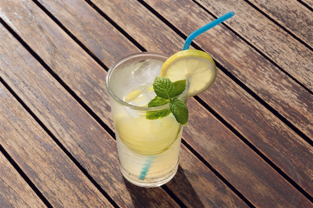 Fresh lemonade in glass with straw on a wooden table