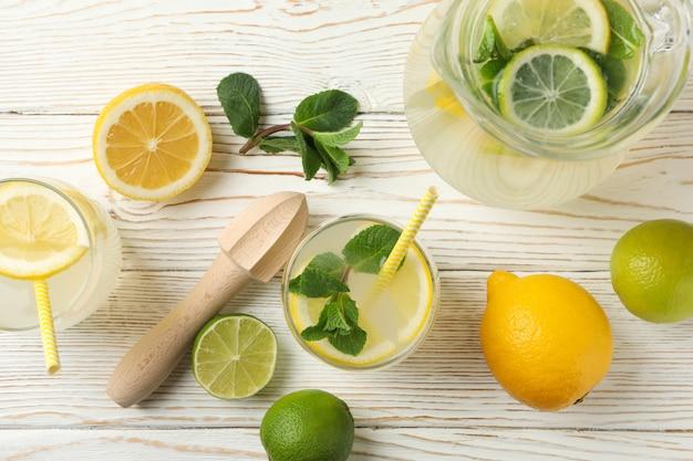 Свежий лимонад в разных стаканах на деревянной поверхности, вид сверху