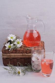 유리와 흰색 테이블에 데이지와 항아리에 신선한 레모네이드.