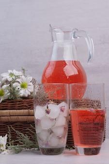白いテーブルの上にデイジーとガラスと瓶の新鮮なレモネード。