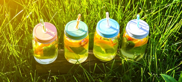 ストローの瓶に新鮮なレモネード。流行に敏感な夏の飲み物。自然の中で環境にやさしい。ガラスにミントが入ったレモン、オレンジ、ベリー。屋外の緑の高い草。